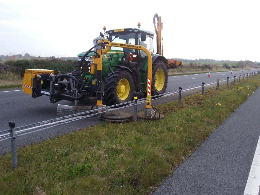 A tractor with a barrier mower cutting grass on the A55