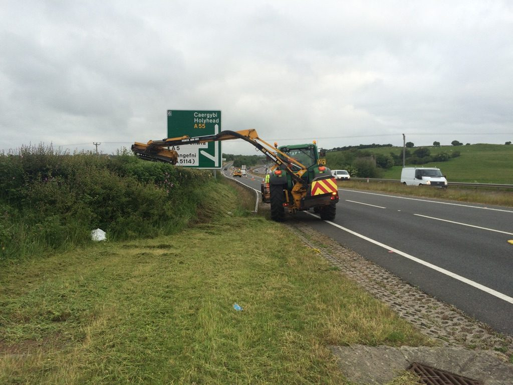 A tractor and operator trimming hedges on the A55 on Anglesey